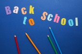 top view of back to school lettering with pencils on blue background