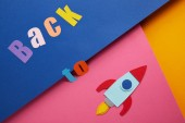 Photo flat lay with back to lettering and rocket on colorful paper background