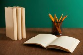 Fotografie open textbook, books and pencils on wooden table