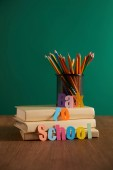 Fotografie colorful pencils and books on wooden tabletop with back to school lettering