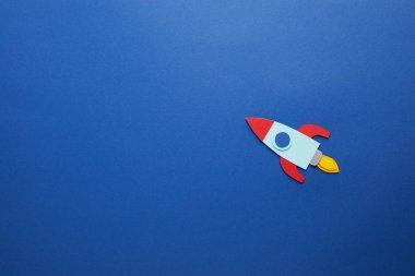 creative rocket on blue paper background