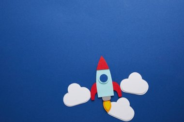 Clouds and rocket on blue background with copy space stock vector