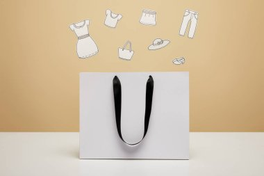paper clothes above white shopping bag on white table isolated on beige