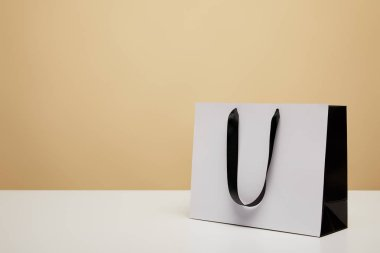 one white shopping bag with black handle on white table isolated on beige