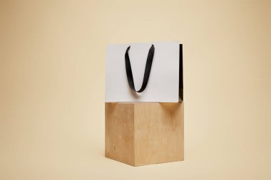 one shopping bag on wooden cube isolated on beige