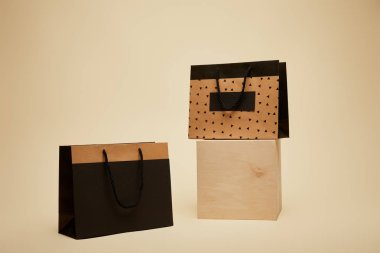 one shopping bag on wooden cube, black paper bag on beige surface
