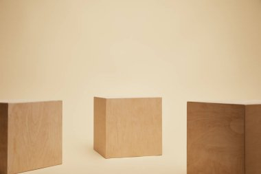 three brown wooden cubes isolated on beige