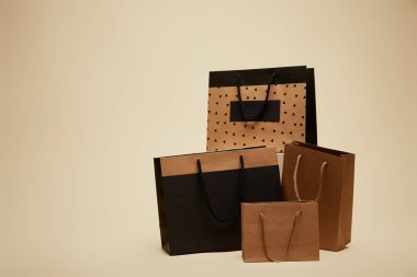 four different shopping bags isolated on beige