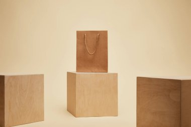 paper shopping bag and three wooden cubes isolated on beige