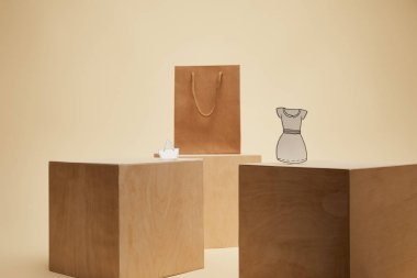 shopping bag, paper bag and paper dress on wooden cubes isolated on beige