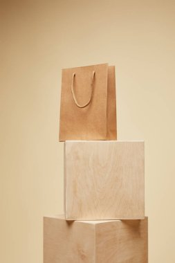 shopping bag on wooden cubes isolated on beige