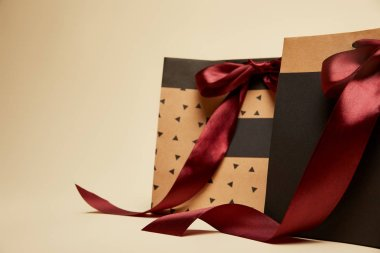 fashionable brown and black shopping bags with bows isolated on beige