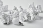 Fotografie close-up shot of energy saving light bulb with crumpled papers on white