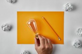 Fotografie cropped shot of man holding incandescent lamp on blank yellow paper with pencil surrounded with crumpled papers on white surface