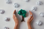 Fotografie cropped shot of woman covering crumpled papers in shape of tree on white surface