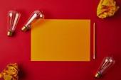 piros felületén sárga üres papír gyűrött papír és izzólámpák felülnézet
