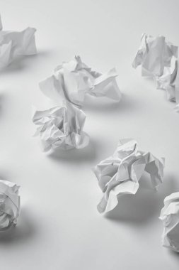 close-up shot of spilled crumpled papers on white surface