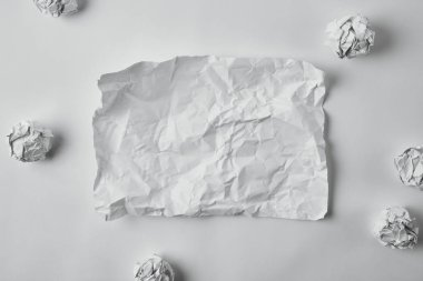 top view of blank damaged paper surrounded with crumpled papers on white surface