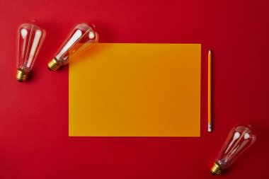 top view of blank yellow paper with pencil and incandescent lamps on red surface
