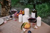 Fotografie candles and red wine on table in garden