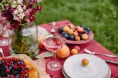 Photo berries pie, wineglass and bouquet of flowers on table in garden