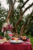 Photo bouquet of flowers, fruits and wineglass on table in garden