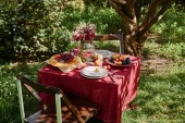 Fotografie bouquet of flowers, fruits and pie on table in garden