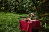 Fotografie bouquet of flowers, wineglasses and fruits on table in garden