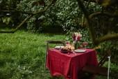 Fotografie kytice květin, pohárky a ovoce na stole v zahradě