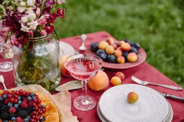 berries pie, wineglass and bouquet of flowers on table in garden