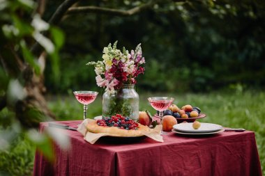 bouquet of flowers in glass jar, fruits and wineglasses on table in garden