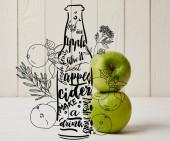 Svěží zelená jablka na dřevěné pozadí s ukázkou láhev jablečného