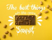 Fotografie Top view of chocolate bar with scattered iris milk candies isolated on yellow with the best things in life are sweet lettering