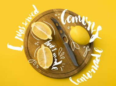 Top view of lemons and knife on a wooden board isolated on yellow with
