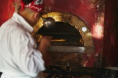Fotografia ritagliata colpo dello chef prendendo pizza dal forno a legna presso la cucina del ristorante