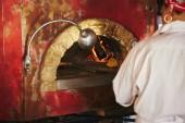 Fotografia ritagliata colpo dello chef prendendo la pizza dal forno di mattoni a cucina del ristorante