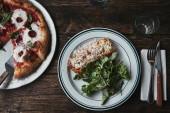 Fotografia vista superiore di pizze appena sfornate e lasagne sulla tavola di legno