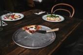 Fotografia fetta di pizza saporita con server sul vassoio di metallo e tavolo in legno con piastre di lasagne e cagliata frittelle