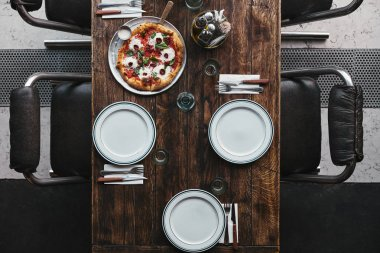top view of delicious pizza on tray and table setting at restaurant
