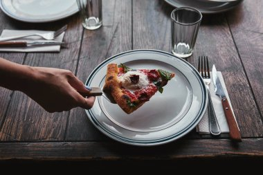 cropped shot of woman serving slice of pizza margherita on plate at restaurant