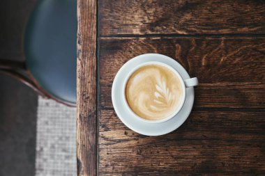 top view of cup of coffee with latte art on rustic wooden table