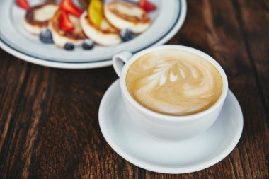 close-up shot of tasty cheese pancakes on plate and cup of coffee on rustic wooden table