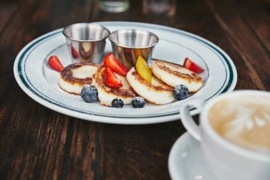 delicious syrniki on plate and cup of coffee on rustic wooden table