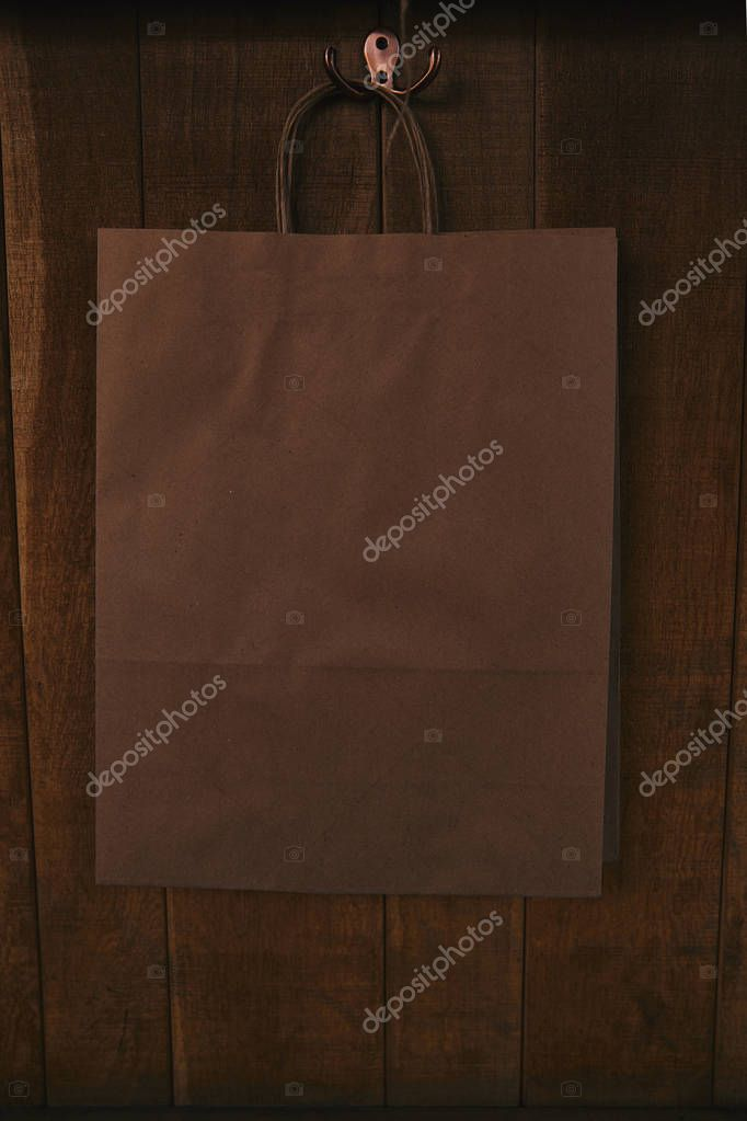 Blank paper bag hanging on wooden wall stock vector