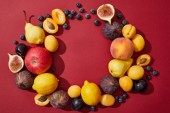 top view of various fresh ripe sweet summer fruits on red background