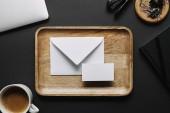 lapos feküdt a fa tálca üres névjegykártya és fekete háttér, a laptop és levélpapír boríték