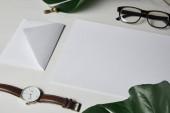 Fotografia Modello di lettera con gli occhiali e Guarda su priorità bassa di marmo bianco con monstera lascia