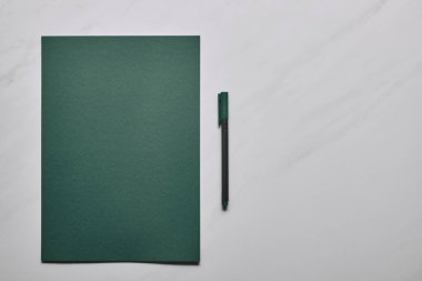 Green paper and pen on white marble background