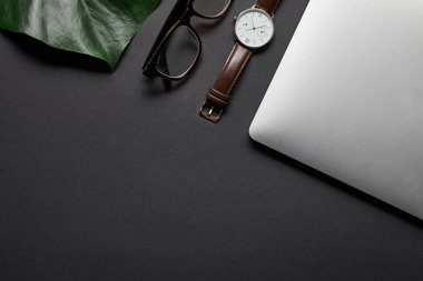 Laptop with glasses and watch on black background with green leaf