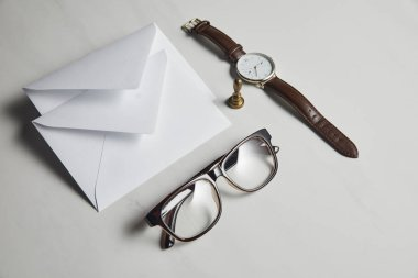White envelops with glasses and watch on white marble background